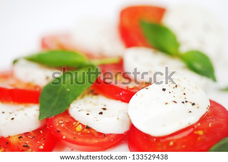 Tomato and mozzarella with basil leaves on a plate - stock photo