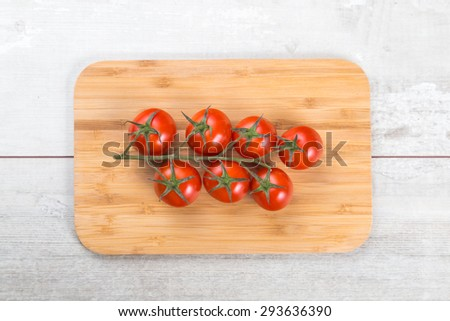 Tomato branch on vintage wood table. - stock photo
