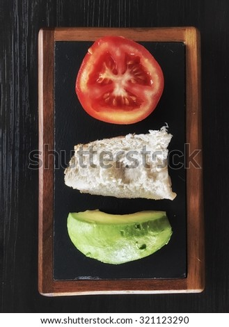 Tomato, bread and avocado plate - stock photo