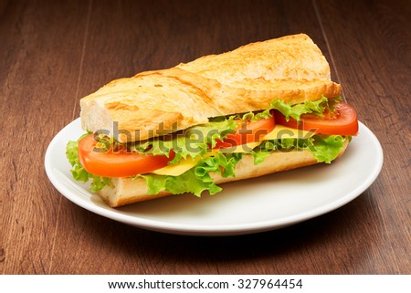 Tomato, cheese and salad sandwich from fresh baguette on white ceramic plate on dark wooden table background - stock photo