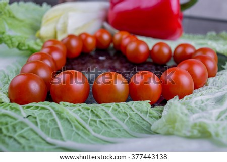 Tomato cherry heart on table background.Shape heart of tomatoes on table background surrounded with vegetables.