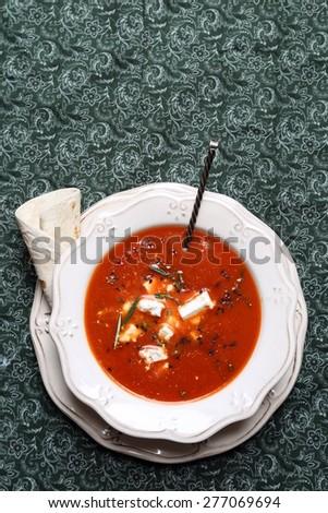 Tomato cream soup, seasoning on a green tablecloth - stock photo