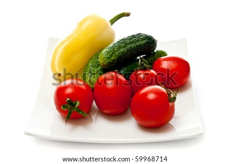 Tomato, cucumber and pepper in plate isolated on white background