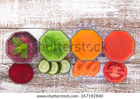 Tomato, cucumber, carrot, beet Juices and vegetables on white wooden table top view. - stock photo