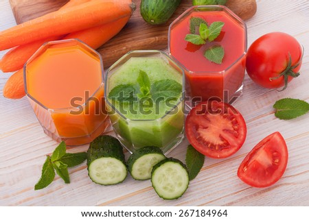 Tomato, cucumber, carrot Juices and vegetables on white wooden table top view - stock photo