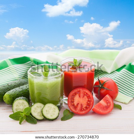 Tomato, cucumber Juices and vegetables on white wooden table. Blue sky with clouds - stock photo