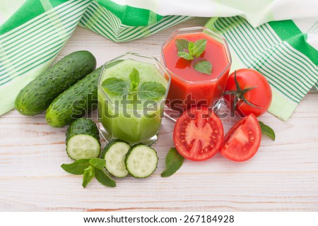 Tomato, cucumber Juices and vegetables on white wooden table top view - stock photo
