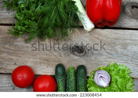 Tomato, cucumber, lettuce, parsley, dill, paprika, leek, onion - fresh vegetables lie on wooden board background with free space in center - stock photo