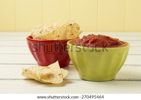 Tomato dip and nachos (corn chips for dipping) on a white wooden table. - stock photo