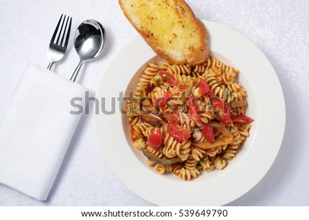Tomato Fusili Pasta Vegetarian dish with garlic bread
