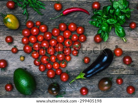 Tomato heart shape and vegetables as healthy eating concept on wooden table it rustic style - stock photo