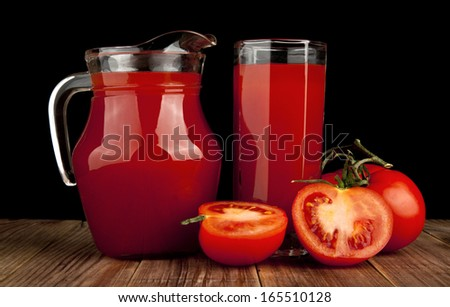 tomato juice and tomatoes on a black background - stock photo