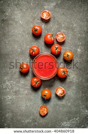 Tomato juice and whole tomatoes. Wet stone background.  - stock photo