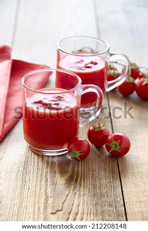 Tomato juice glasses with cherry tomatoes on wooden table