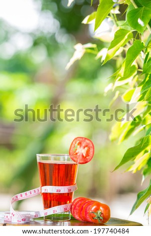 tomato juice healthy fruit and tape measure placed on the table in the morning. - stock photo