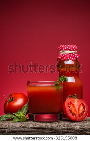Tomato juice in a glass on a rustic wooden table