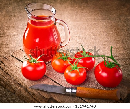 Tomato juice in glass jar, fresh organic tomatoes, steel knife on wooden cutting board and linen background. Image in vintage style