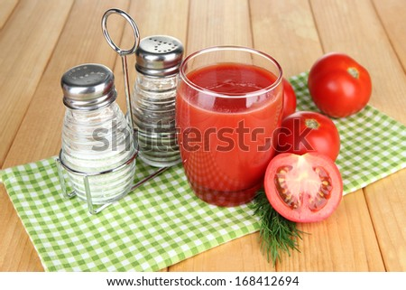 Tomato juice in glass, on wooden background - stock photo