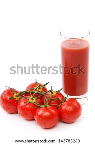 Tomato juice in glass with a cluster of tomatoes - stock photo