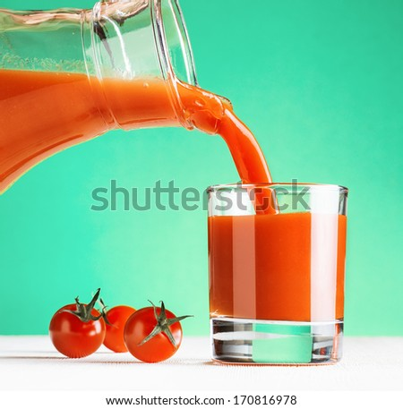 Tomato juice pouring from jug into a glass. Green background. - stock photo