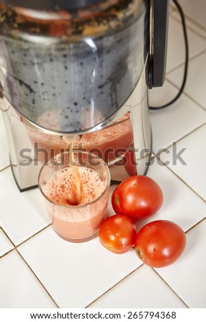 Tomato Juicer flow its liquid to a glass - stock photo