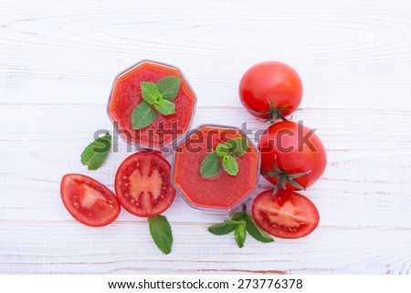 Tomato Juices and vegetables on white wooden table top view - stock photo
