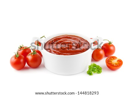Tomato ketchup in a white bowl with tomatoes on white