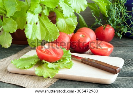 Tomato, lettuce and knife on board.Thyme on wooden background. Ingredients for salad - stock photo