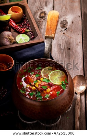 Tomato mexican soup with spices and lime on wooden table.Selective focus.