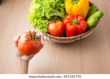 Tomato on hand with fresh vegetable prepared in bowl on wooden table,Kid holding tomato with vegetable ingredient  in bowl on wooden table  preparing for making salad.