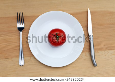 Tomato on plate with knife and fork - stock photo