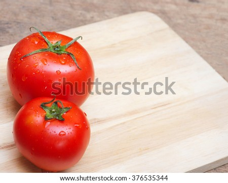 Tomato on the cutting board over wood table