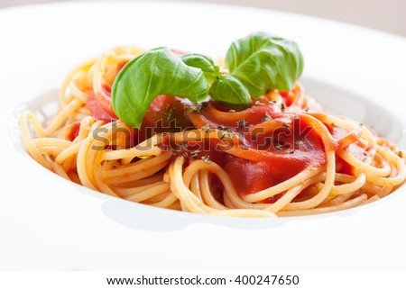 Tomato pasta spaghetti with fresh tomatoes, basil, italian herbs and olive oil in a white bowl on a white wooden background, closeup  - stock photo