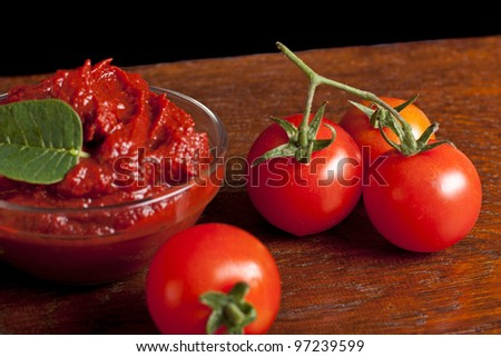 Tomato paste and some tomatoes on wood - stock photo