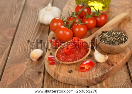 Tomato paste in wooden spoon on brown background - stock photo