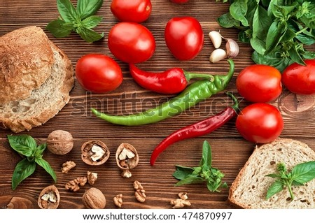 Tomato, pepper, basil, nuts and bread on old wood table