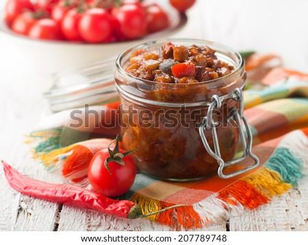 Tomato, pepper, eggplant and zucchini preserves in glass jar, selective focus  - stock photo