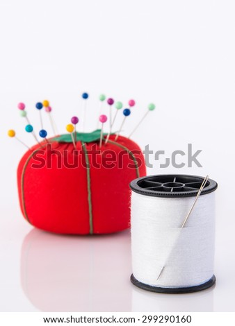 Tomato pin cushion and spool of thread - stock photo