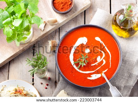 Tomato, red pepper soup, sauce with olive oil, rosemary and smoked paprika on a wooden background. - stock photo