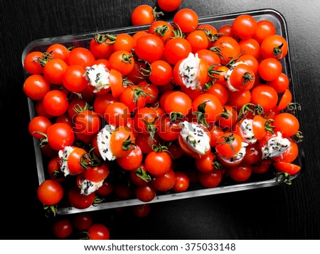 Tomato salad. Group of fresh tomatoes. Cherry tomatoes on black background.