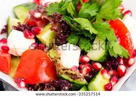 Tomato salad with feta cheese and pomegranate seeds. Macro. Photo can be used as a whole background.