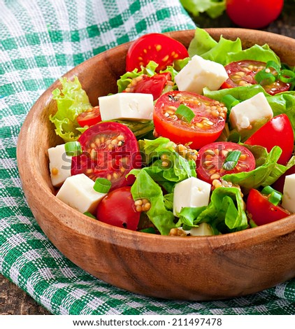 Tomato salad with lettuce, cheese and mustard and garlic dressing - stock photo