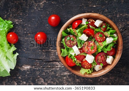 Tomato salad with lettuce, cheese and mustard and garlic dressing. Top view
