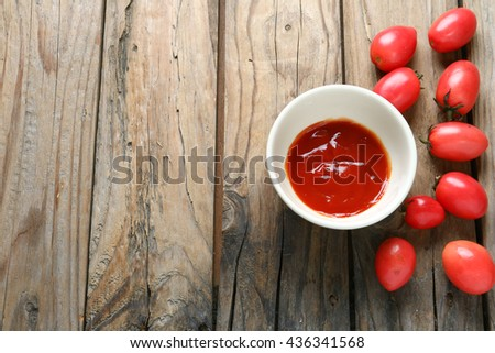 Tomato sauce cups on the wooden floor - stock photo