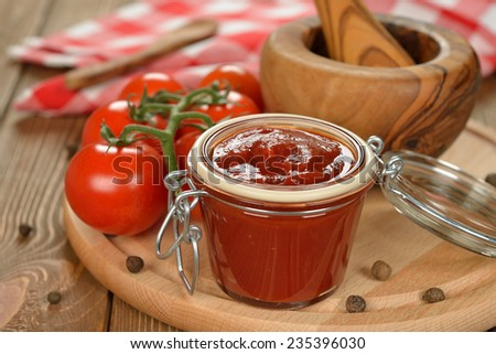 Tomato sauce in a glass jar on a brown background - stock photo