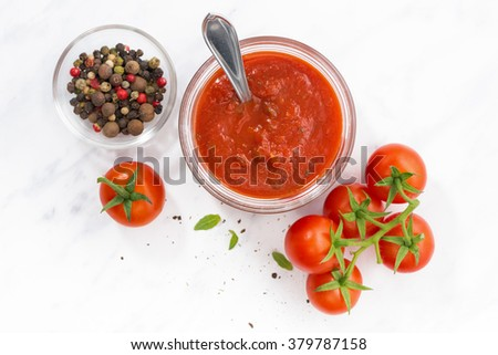 tomato sauce in a glass jar on white background, top view, horizontal
