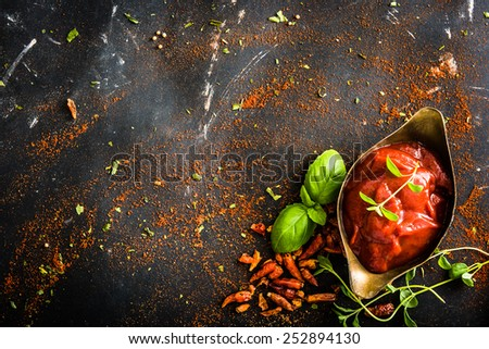 tomato sauce in a gravy boat and spices on textured black background - stock photo