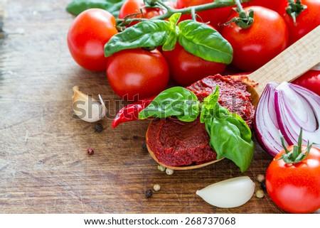 Tomato sauce ingredients - cherry tomatoes, onion, basil, garlic, chili, pepper, wood board, top view - stock photo