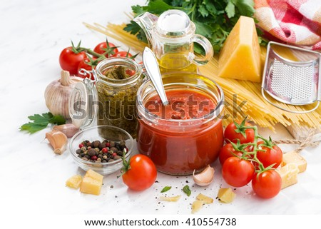 tomato sauce, pesto and ingredients for pasta on a white table, closeup - stock photo