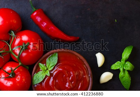 Tomato sauce salsa and ingredients - tomatoes, garlic, chili on dark stone background. Top view - stock photo